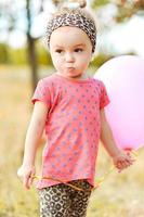 doce menina com balão ao ar livre foto