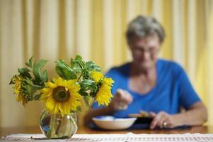 mulher idosa comendo sozinho