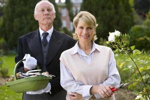 mulher com tesouras de podar mordomo com cesta de ferramentas de jardinagem foto