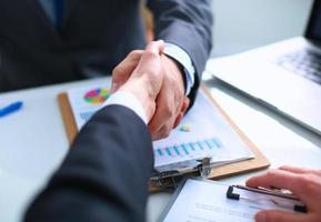 Empresários apertando as mãos, terminando uma reunião foto