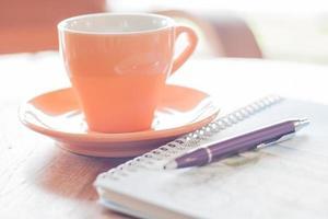 caderno de caneta e espiral com xícara de café foto