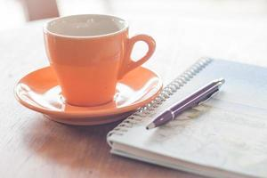 xícara de café com caneta e caderno espiral foto