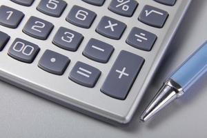 caneta e calculadora em papel comercial foto