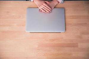 laptop em cima da mesa com mãos femininas foto