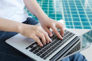 mulher que trabalha com o computador portátil, sentado na piscina foto