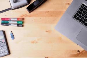 equipamento de escritório e laptop na mesa de madeira foto