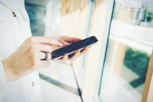 telefone inteligente, segurando na mão feminina, ela está usando um foto