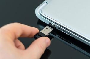mão ligar usb flash drive para laptop. foto