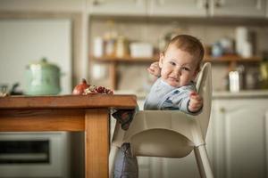 retrato de menino jovem feliz na cadeira alta foto