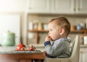criança feliz com romãs, sentado à mesa foto