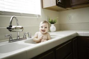 bebê na pia da cozinha foto