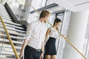 empresário e empresária andando e tomando escadas foto