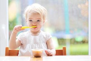 menina criança comendo purê de maçã amassado saboroso foto
