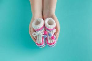 mão segurando pequenas botas de malha foto