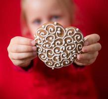 menina com pão de mel em forma de coração foto