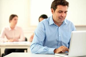homem profissional trabalhando e olhando em seu laptop foto