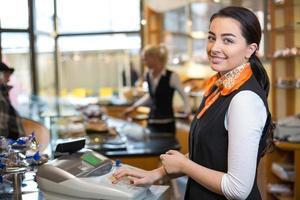 lojista e vendedora na caixa registradora foto