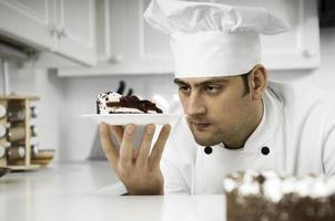 chef examinando atentamente o prato de sobremesa foto