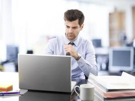jovem empresário trabalhando no laptop foto