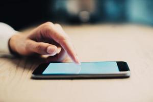 telefone inteligente usando na mão feminina em cima da mesa foto