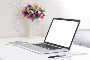 mesa de escritório com computador portátil de tela em branco foto