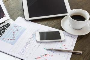 xícara de laptop, tablet, smartphone e café com documentos financeiros foto