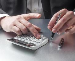 mananger de finanças contando com calculadora foto
