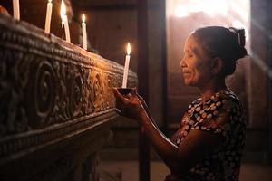 mulher asiática rezando com luz de velas
