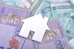 forma da casa com nota de banco da Malásia, conceito de finanças