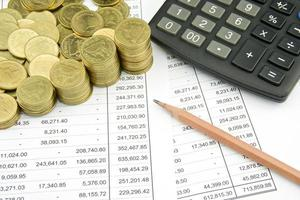 moeda na conta de finanças com lápis e calculadora foto