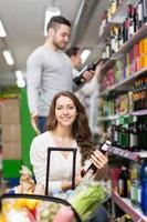 compradores escolhendo a garrafa de vinho na loja de bebidas foto