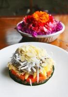 sobremesa exótica crua no prato branco com flores no fundo foto
