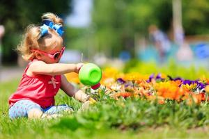 menina regando flores no verão foto