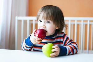 adorável criança comendo maçãs foto
