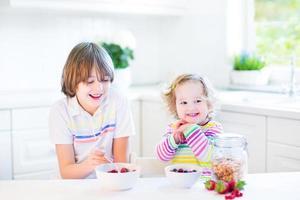 menino adolescente e sua irmã bonito da criança na cozinha ensolarada foto