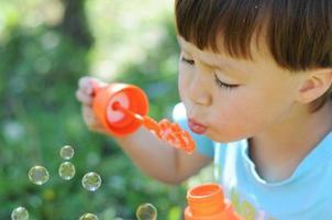 menino soprando bolhas foto