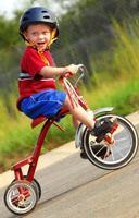 menino feliz no triciclo foto