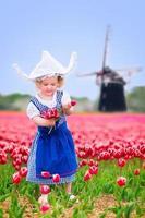 menina bonita em traje holandês no campo de tulipas com moinho de vento