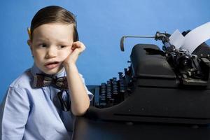 um jovem rapaz vestido como um repórter sentado em uma máquina de escrever foto