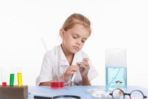 menina com um par de pinças em laboratório foto