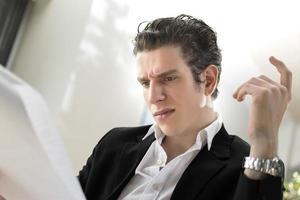 negócio masculino olhando pensando em seus papéis foto