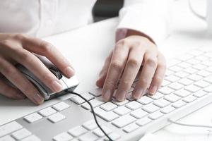 mulher que trabalha na mesa, teclado e mouse foto