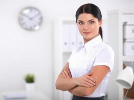 mulher de negócios atraente com os braços cruzados em pé no escritório foto