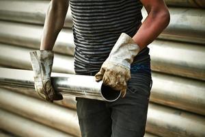 trabalhador da construção carregando cano de ferro