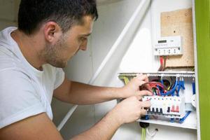 eletricista conectando um novo disjuntor a um imóvel residencial foto