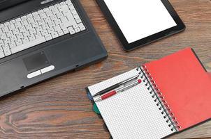 laptop e material de escritório na mesa de madeira foto