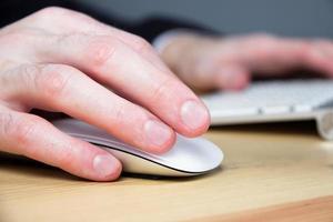 mão do homem com mouse de computador sem fio foto