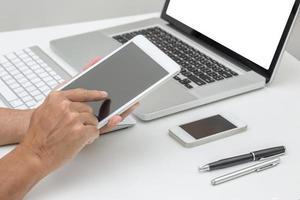 mãos de homem segurando o tablet com fundo de computador portátil foto