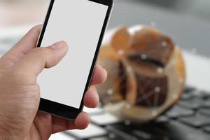 close da mão segurando a tela em branco do telefone inteligente foto