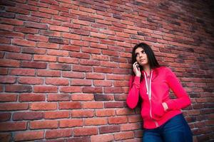 jovem mulher falando ao telefone por cima da parede de tijolos foto